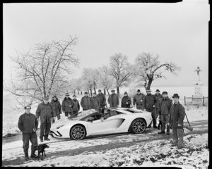 Group of men with dogs near a fancy car